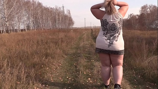 A beautiful mature BBW walks outdoors and shake...