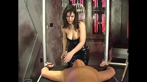 Busty chick in a latex dress ties a guy to the table and punishes him with a whip Thumb