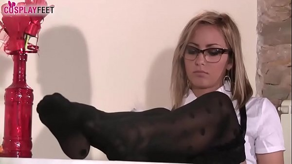 Schoolgirl in black dotted stockings plays with...