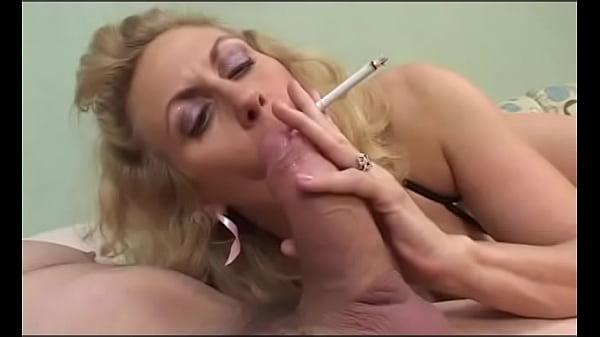 Mature broad smokes cigarette while sucking dick