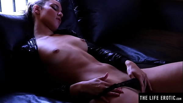 Beauty in leather thrusts her fingers into her soaking wet pussy