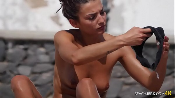 Tanned toned brunette shows off her tits on topless beach Thumb