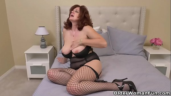 Busty milf Andi James dips two fingers into her pussy