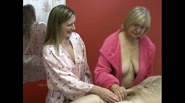 Senior masseuse helps junior masseuse in jerking off a naked client
