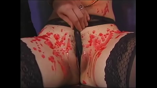 Redhead in latex lingerie beats a young chick hard with a whip in BDSM room