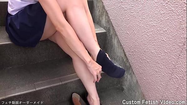 Student girl walks in the park taking off socks...