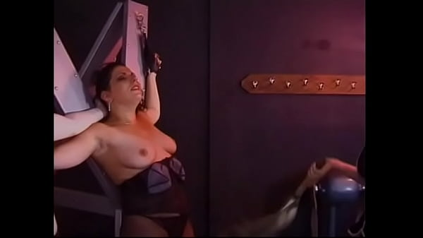 Red-haired bitches in latex costumes tie a pretty brunette to the cross and smack her