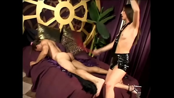 Muscular dude wears a collar and licks his mistress's legs in latex lingerie