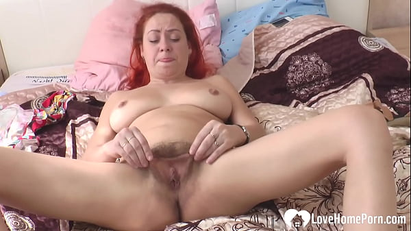 Hairy redhead moans while playing with herself