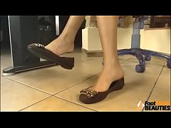 Barefoot brunette shows her soles and ballet flats