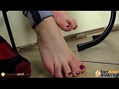 Barefoot brunette gives herself a foot massage ...