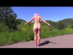 Sexy nudist in a public place jumps on a jump r...
