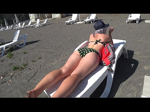 Juicy booty in shorts goes outdoors, changes clothes in a public booth on the beach, bathes and sunbathes. Fetish with peeping.