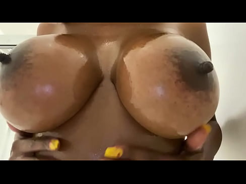 Shy ebony oils her tits in the shower