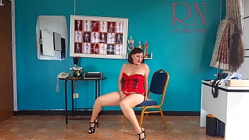 An elegant lady employee in red lingerie undresses in the office. 1