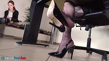 Redhead secretary gives sexy tease with her feet in nylons